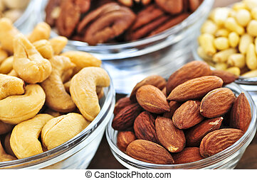 Almonds, cashews pistachio and pine nuts in glass bowls