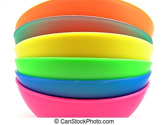 Bowls of various colors next to each other surrounded by...
