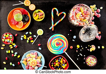 Bowls of yummy jelly beans and licorice rolls besides large...