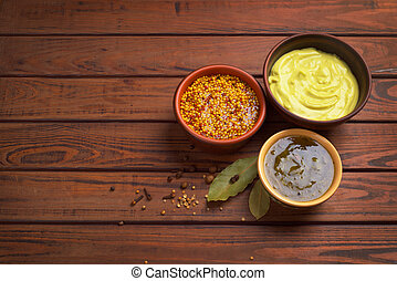 bowls with sauces on a wooden background