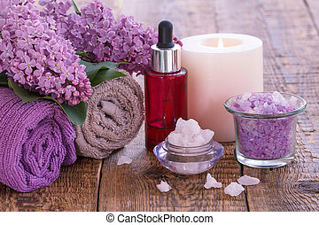 Bowls with sea salt, burning candle, red bottle with aromatic oil, lilac flowers and towels on wooden boards.