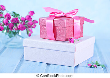 box for present and flowers on a table