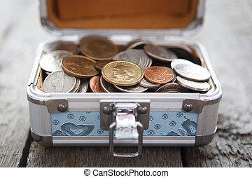 Box for savings full of coins.
