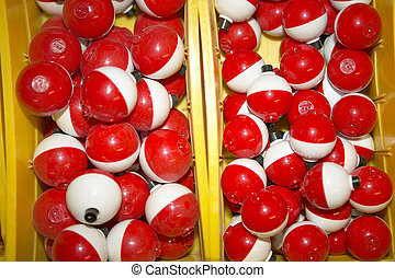Box full of red and white plastic bobbers or floats to ...