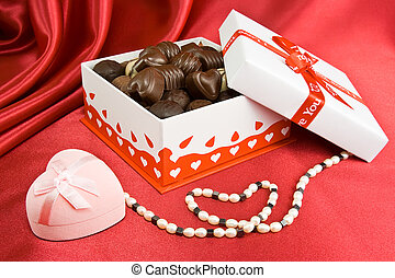 Box of chocolates with present and pearls.