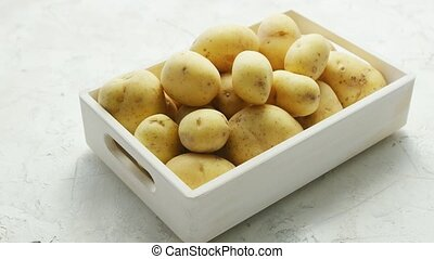 Box of clean and washed potatoes - White container filled...