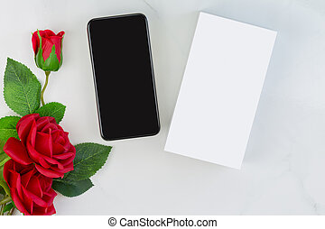 Box of new Smartphone phone next to red roses on marble...