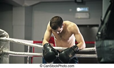 Box training - a tired man leaning on the fencing of the ring