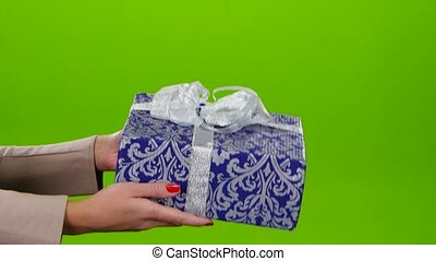 Box with a gift lovingly packed in blue paper with ornament,...