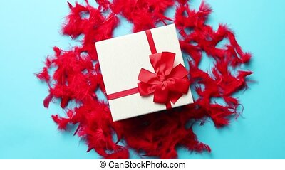 Box with a gift, tied with a ribbon placed on red feathers....