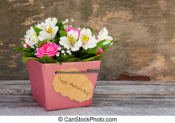 Box with flowers on old wooden background. Concept of greeting Happy Mother's Day.