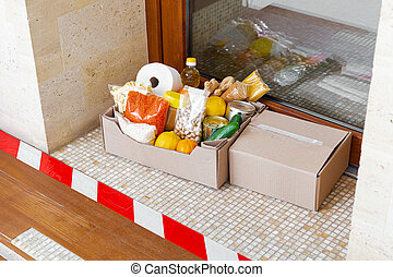 Box with food during self-isolation covid quarantine at home. Food box delivery on doorstep near door behind the line. Contactless delivery, safe shopping. Social distance concept