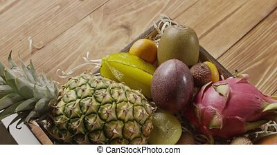 Box with fresh natural tropical fruits on a wooden table....