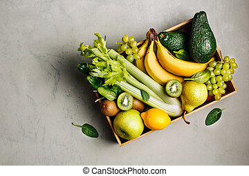 Box with fruits and green vegetables.