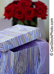 Box with gift on a background of bouquet red roses