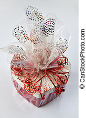 box with gift packed in cellophane on light background