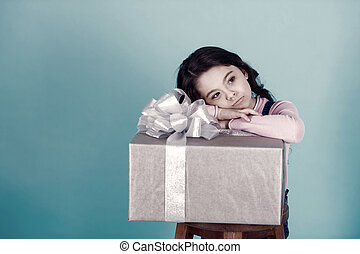 Box with ribbon bow and little girl