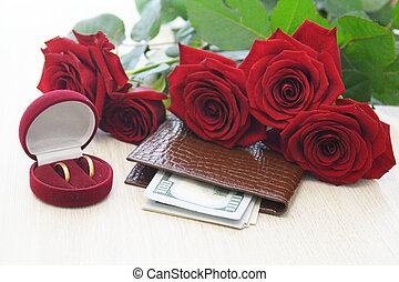 box with two rings, red roses and dollars on the table