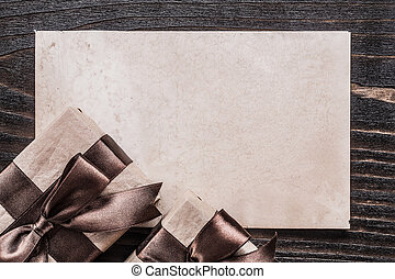 Boxed gifts with tied ribbons paper on wooden board.