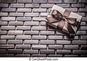 Boxed present with ribbon on wooden wicker matting holidays...
