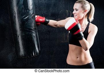 boxeo, entrenamiento, mujer, saco de arena, en, gimnasio