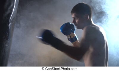 The boxer will puncture the boxer's pear in wet blue boxing gloves. Black background 4K