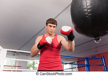 Boxer doing some training on punching bag at gym. Young caucasian boxer training with punching bag in gym