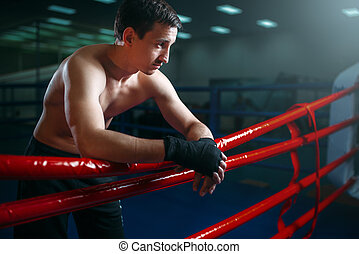 Boxer in black bandages poses on ring ropes