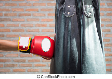 Boxer in red boxing gloves is punching a sandbag