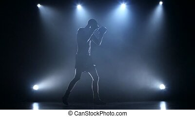 Boxer in the spotlight is trained in studio. Slow motion -...