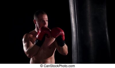 boxer man during boxing hiting heavy bag at training fitness gym. Slow motion.