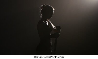 Boxer shakes special bandages on his hands. Silhouette. Black background . Side view. Close up