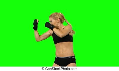 Boxer standing in the front and make swings and kicks. Green screen. Side view. Close up