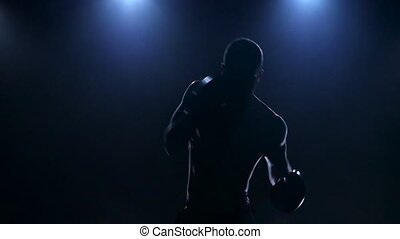 Boxer training in the dark studio. Slow motion in silhouette