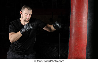 Boxer training on a punching bag in the gym