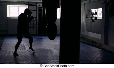 Boxer trains with punching bag in the dark gym. 4k