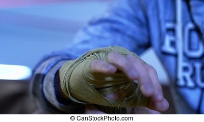 Boxer wrapping bandages on his hand before fight. Close up....
