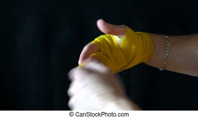 boxer yellow unwinds the bandages after the fight.