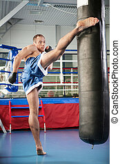 Boxer. Young confident kickboxer training at the punching...