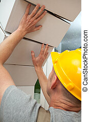 White and heavy boxes falling on worker with yellow helmet