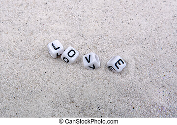 Boxes with love inscription on a grey sand