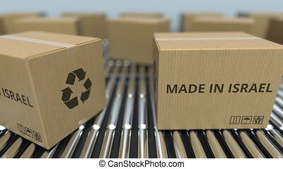 Boxes with MADE IN ISRAEL text on roller conveyor. Israeli...