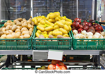 Boxes with ripe fresh potatoes and onions on shelves