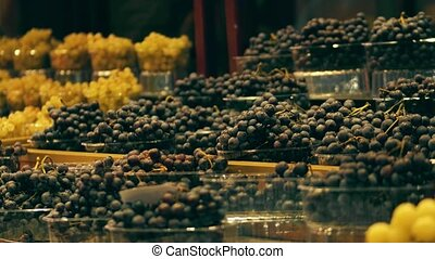 Boxes with white and black grape at fruit stall on the...