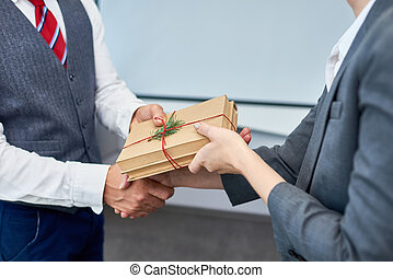 Close up view of unrecognizable businessman shaking hands with female colleague presenting her gift for Boxing Day