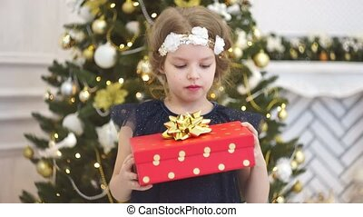 Boxing day. Little girl rejoices to a Christmas gift.