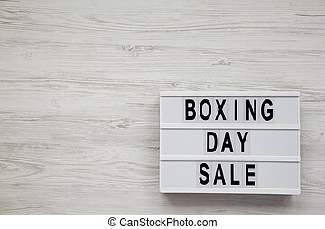 'Boxing day sale' words on a lightbox on a white wooden background, top view. Overhead, from above. Copy space.