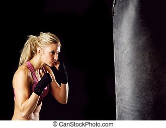 Boxing Girl - Young female in 20s boxing on a punching bag.