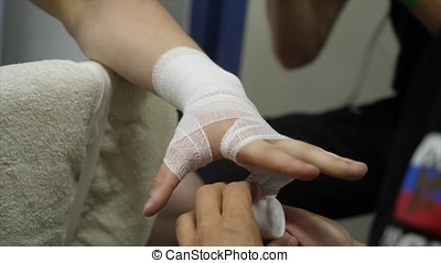 Boxing Trainer or Manager Wrapping Hands of a Boxer Close Up Shallow Depth of Field - Preparing For Boxing Match - Doctor Wrapping Possible Fractured or Broken Hand of Injured Person