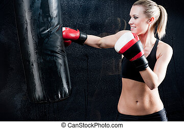 Boxing training woman punching bag in gym - Boxing training...